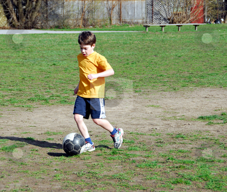 Boy playing soccer stock photo, Young boy playing soccer by Elena Elisseeva