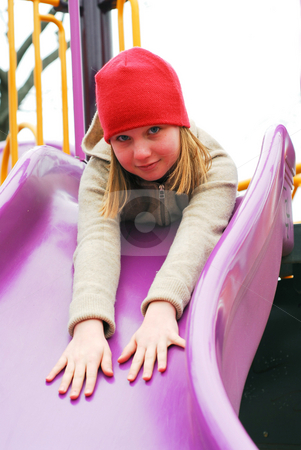 Girl on playground stock photo, Young girl in a red hat on playground, about to go down the slides by Elena Elisseeva