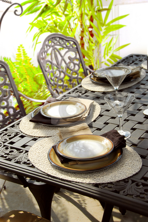 Table setting stock photo, Table setting on a patio table with plates and martini glasses by Elena Elisseeva
