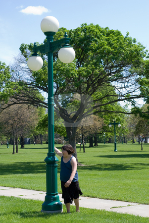 Girl Spinning stock photo, A young girl spinning around a light pole by Richard Nelson
