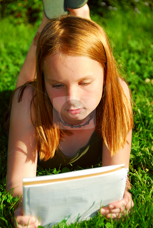 Girl grass stock photo, Young girl lying on green grass outside with a notepad by Elena Elisseeva