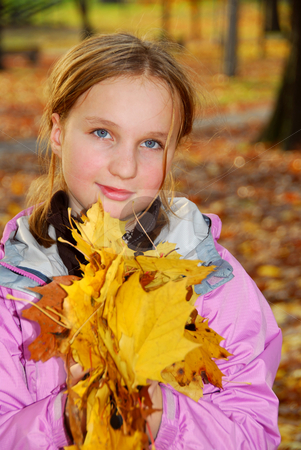 Girl with leaves stock photo, Young girl holding a pile of autumn maple leaves by Elena Elisseeva