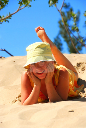 Girl dunes stock photo, Young girl in yellow hat lying on top of a sand dune by Elena Elisseeva