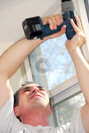 Handyman stock photo, Man drilling a hole in a ceiling by Elena Elisseeva