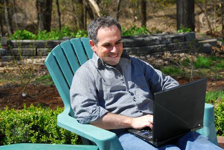 Man computer outside stock photo, Man working on a thinkpad outside by Elena Elisseeva