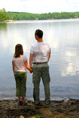 Father daughter lake stock photo, Father and daughter standing on the lake shore and looking at calm water by Elena Elisseeva
