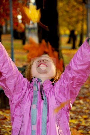 Autumn girl stock photo, Portrait of a young girl throwing autumn leaves by Elena Elisseeva