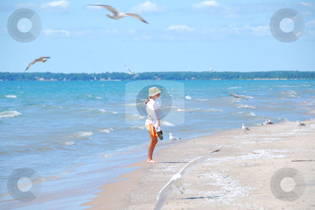 Girl beach seagulls stock photo, Young girl on a beach among flying seagulls by Elena Elisseeva
