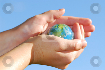Hands globe stock photo, Child holding a globe in hands on blue background by Elena Elisseeva