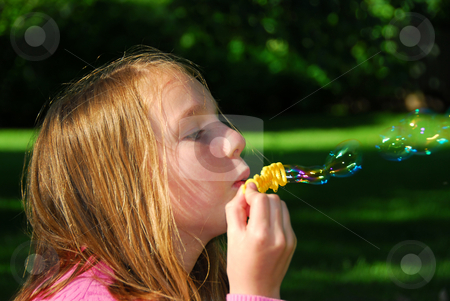 Girl bubbles stock photo, Young girl blowing soap bubbles in a park by Elena Elisseeva