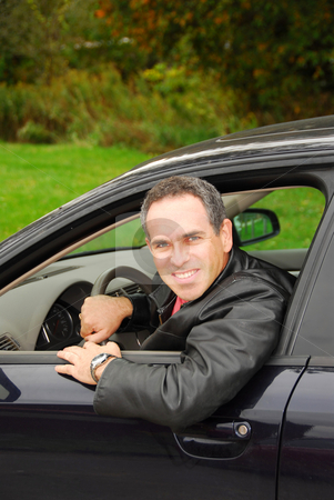 Man in car stock photo, Smiling man looking out of a car window by Elena Elisseeva