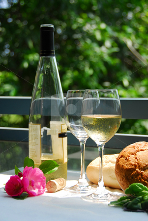 White wine with glasses outside stock photo, Table setting with chilled white wine and glasses alfresco by Elena Elisseeva