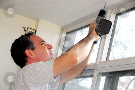Handyman stock photo, Man drilling a hole in a ceiling by Elena Elisseeva