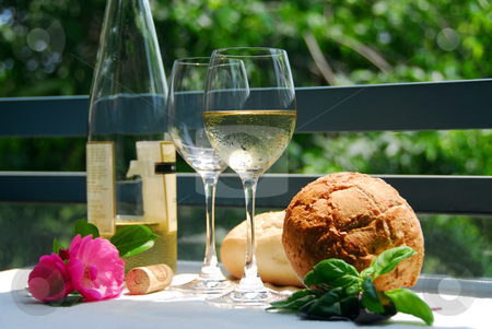 White wine with glasses outside stock photo, Setting with chilled white wine and glasses alfresco by Elena Elisseeva