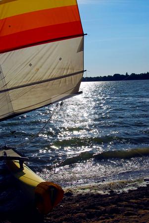 Sailboat backlit stock photo, Catamaran on a beach with backlit sail by Elena Elisseeva