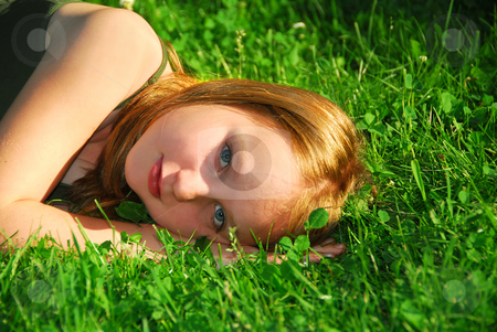 Girl grass stock photo, Young pretty girl lying on green grass outside by Elena Elisseeva