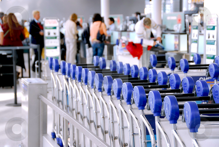 Passengers carts airport stock photo, Luggage carts at modern international airport passengers at check-in counter in the background by Elena Elisseeva