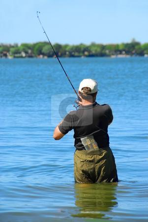 Fisherman stock photo, Man fishing in a lake standing in water by Elena Elisseeva