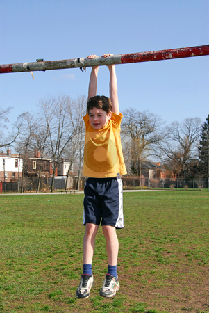 Boy hanging on stock photo, Little boy hanging on the soccer gate by Elena Elisseeva