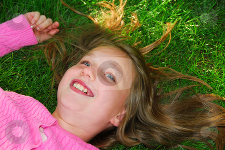Girl grass stock photo, Young girl relaxing on green grass outside by Elena Elisseeva