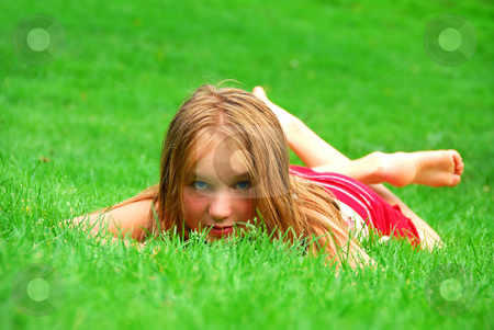 Young girl grass stock photo, Young girl lying on green grass in the summer by Elena Elisseeva