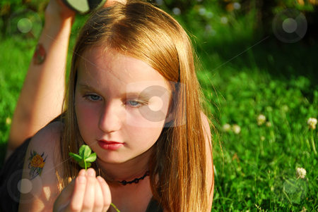 Girl grass stock photo, Young girl lying on green grass outside holding a green plant by Elena Elisseeva