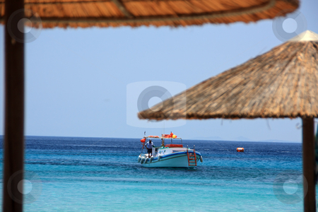 Boat and Beach Umbrellas stock photo, A fishing boat seen through a pair of beach umbrellas in the foreground (Greece) by Georgios Alexandris