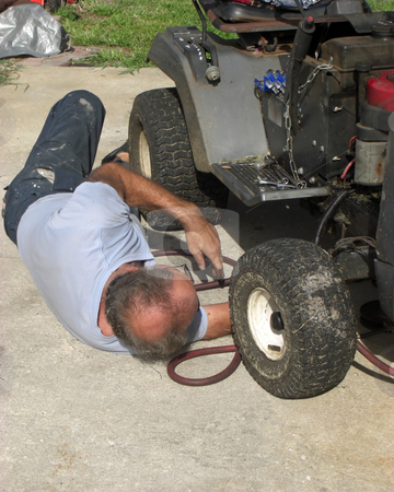 The mechanic stock photo, A man is lying on his back on the ground, and he is repairing an old riding lawn mower by Rebecca Mosoetsa
