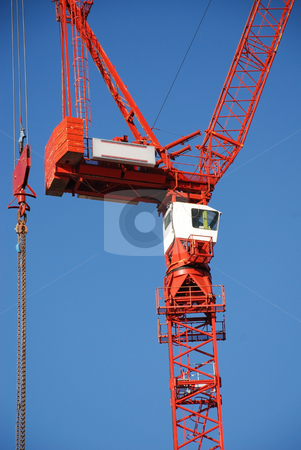 Urban Construction stock photo, A red tower crane undertaking construction work, against a blue sky by Philippa Willitts