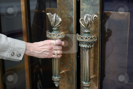 Opening the casino door stock photo, A women's hand prepares to open the door to a Las Vegas casino.  The distinctive door handle with a torch design is on all the entry doors to the strip's New York New York hotel and casino by Dennis Thomsen
