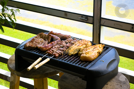 Portable grill stock photo, Bbq grill which is cooking chicken, steak and shish kabobs. by Jose Wilson Araujo