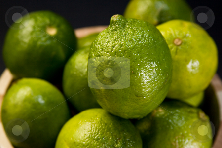 Limes in wooden bowl stock photo, Multiple limes in a wooden fruit bowl by Jose Wilson Araujo