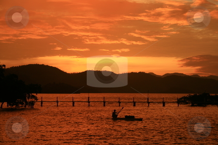 Orange sunset stock photo, Orange sunset with silhouettes of mountain, bridge and boat by Jonas Marcos San Luis
