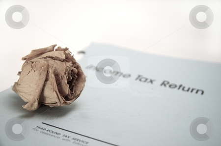 Death and Taxes stock photo, A decaying rose sits on an income tax return, symbolising the saying