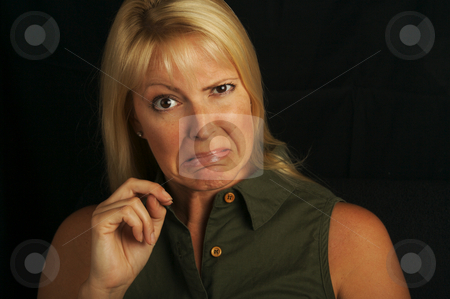 Attractive Expression stock photo, Attractive Blond Haired, Brown Eyed Woman Grimaces on a black background. by Andy Dean