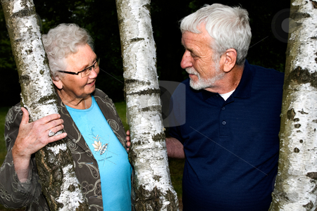 Elderly couple between two trees stock photo, Outside portrait of an elderly couple looking at eachother by Frenk and Danielle Kaufmann