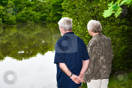 Grandparents watching the lake stock photo, Outside portrait of an elderly couple standing near a lake by Frenk and Danielle Kaufmann