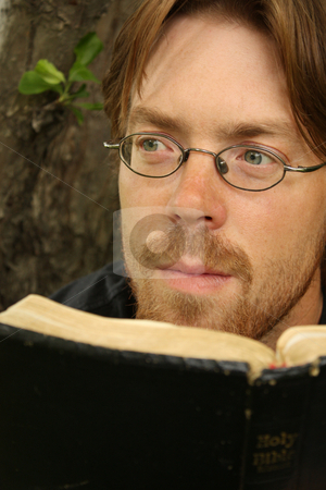 Contemplation stock photo, A man reading a Bible and looking thoughtful. by Jessica Tooley