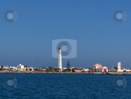 Portugese Lighthouse stock photo, A lighthouse and white buildings in a village in the Algarve region of Portugal. by Jessica Tooley