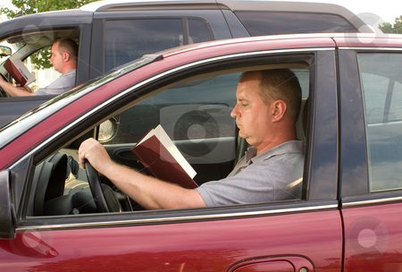 Reading and Driving stock photo, A man reading a book as he drives. by Robert Byron
