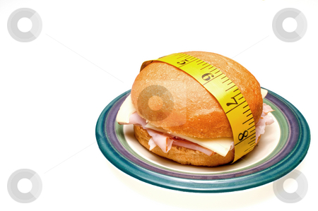 Ham and Swiss Sandwich stock photo, A ham and swiss cheese sandwich wrapped in a taolor's measuring tape. by Robert Byron