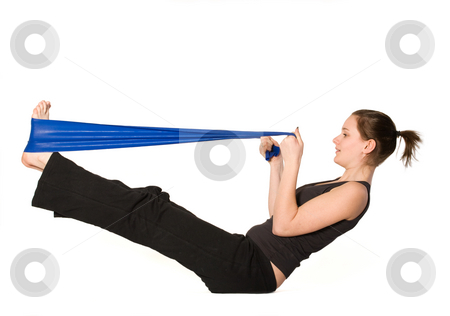 Woman is stretching her legs with a Resistance Band stock photo, Young girl is sporting in the studio on a white background by Frenk and Danielle Kaufmann