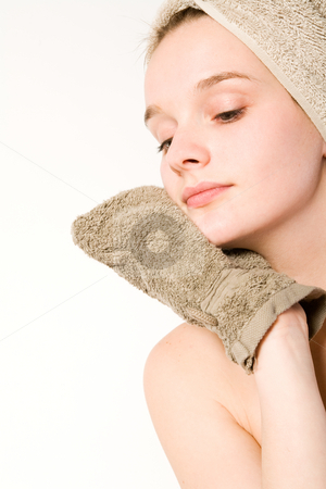 Young woman is cleaning her face stock photo, Young woman in towel on a white background cleaning herself by Frenk and Danielle Kaufmann