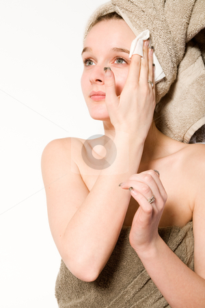 Young girl is cleaning her face stock photo, Young woman in towel on a white background cleaning her face by Frenk and Danielle Kaufmann