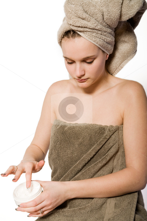 Young woman appying some creme stock photo, Young woman in towel on a white background taking care of herself by Frenk and Danielle Kaufmann