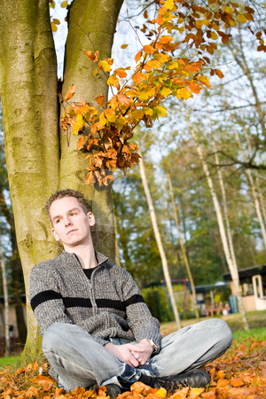Boy is enjoy the sun stock photo, Boy in autumn colors is sitting an enjoy the sun by Frenk and Danielle Kaufmann