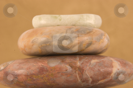 Four Massage Stones stock photo, Stack of hand carved jade massage therapy stones on bamboo mat. by Ariana Bauer