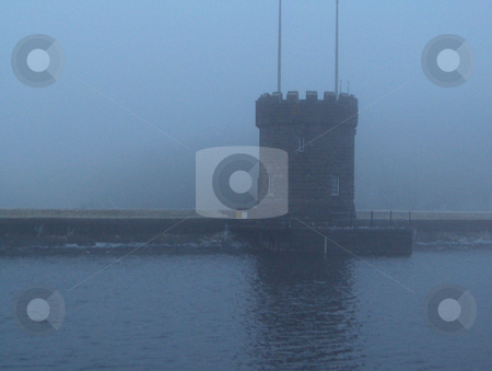 Lonely Keep stock photo, A fortification along the waters of a lake in the Brecon Beacons in Wales on a blue foggy day. by Jessica Tooley