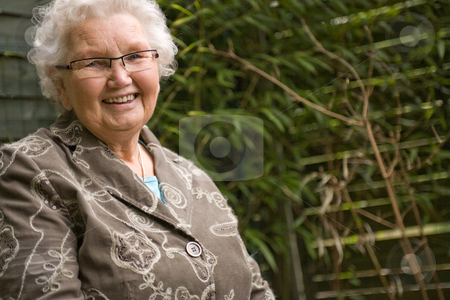 Grey woman sitting relaxed stock photo, Outside portrait of an elderly woman smiling by Frenk and Danielle Kaufmann