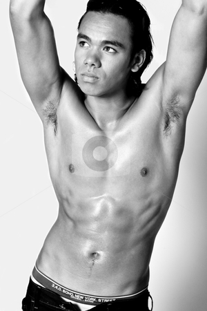 Asian sexy looking boy showing his sixpack stock photo, Studio portrait of a muscular Asian sexy looking boy showing of his six pack by Frenk and Danielle Kaufmann